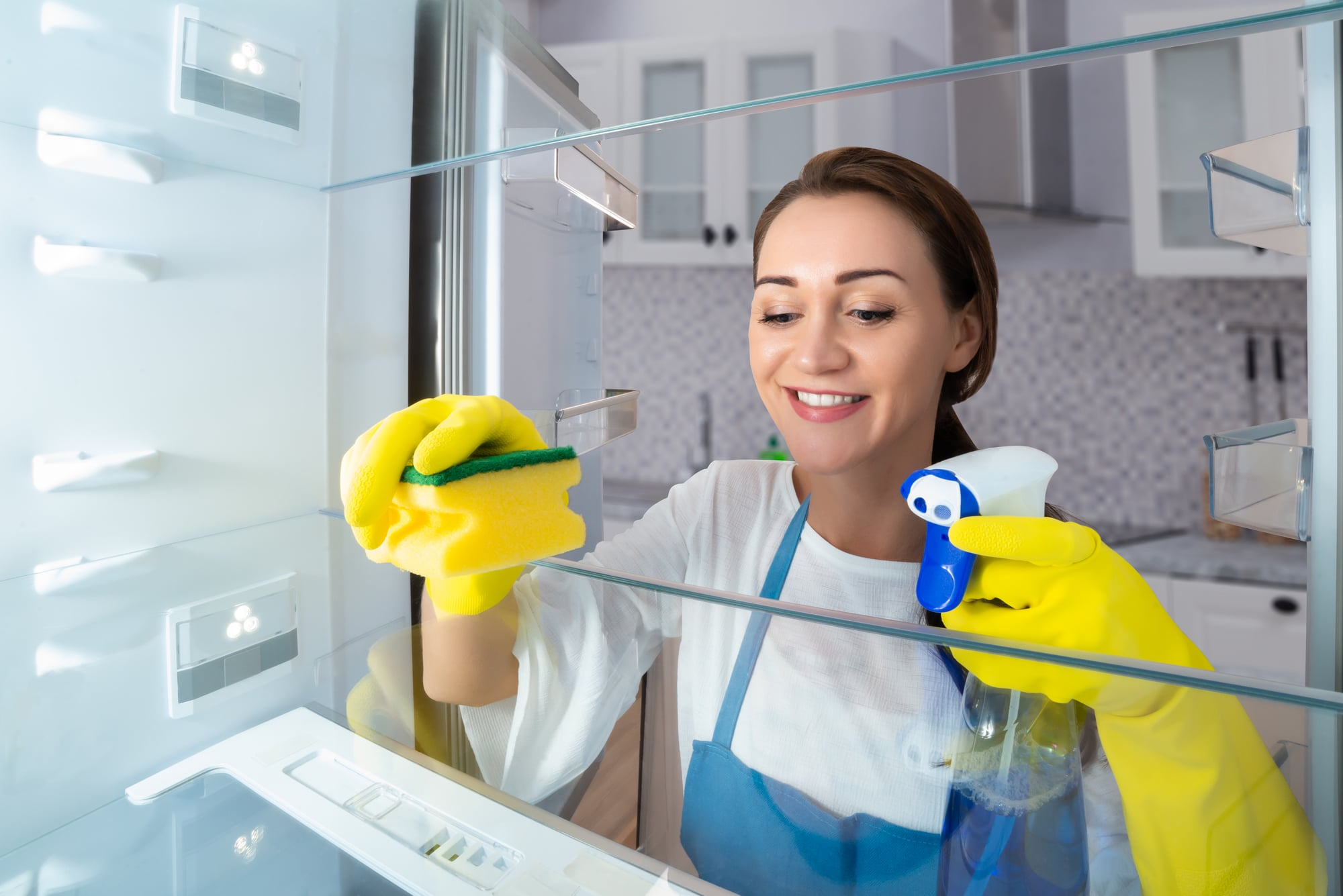 Close-up Of A Happy Young Woman Cleaning Refrigerator With Sponge